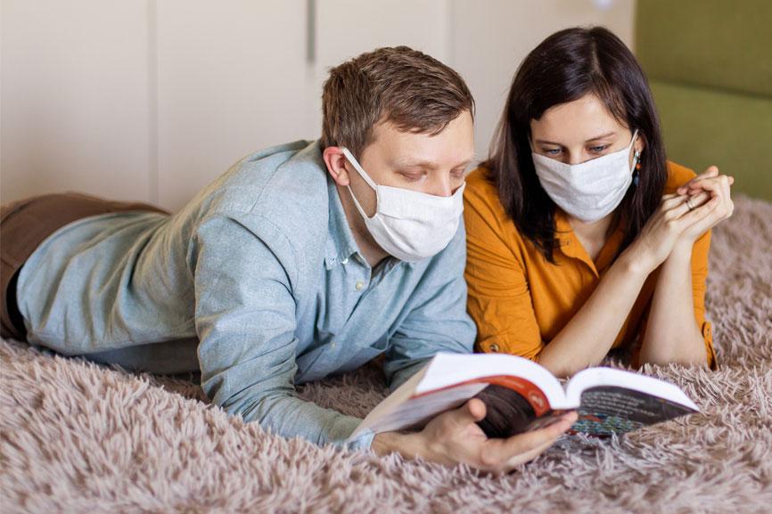 זוג שוכבים על הבטן על המיטה וקוראים ביחד ספר | זוגיות טובה בצל הקורונה